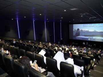 People sitting in a theatre and watching a movie on screen
