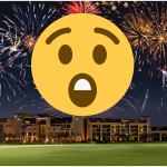A surprised emoji with Firworks in blue sky over green grass and some lit building in the background