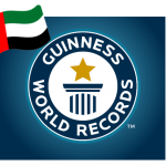 A flag with a vertical stripe and horizontal green, white and black stripes overlaps A logo with text that reads as Guinness World Records and a pictogram with a star atop a pillar
