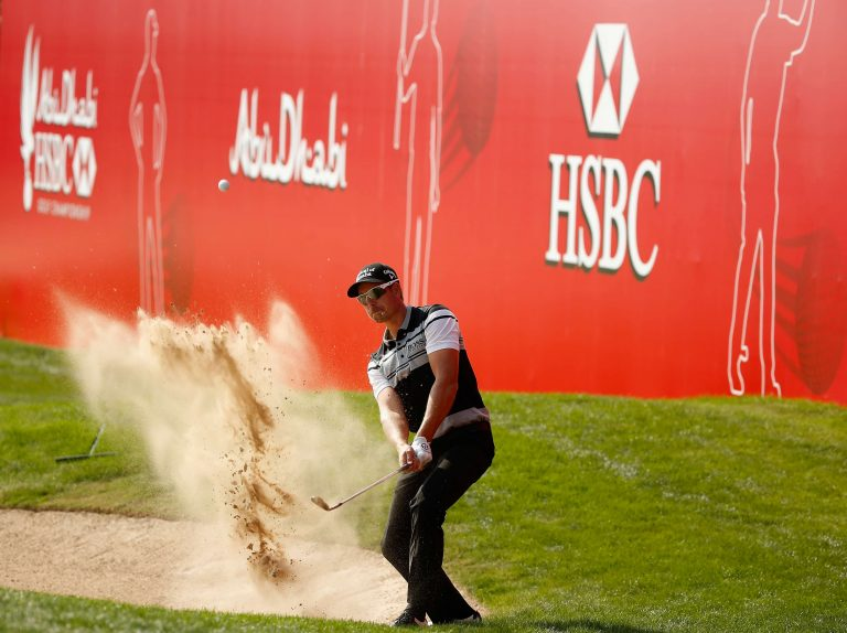 Golfer getting the ball out of sand pit with a swing sending the sand fly in the air