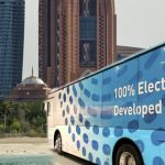 A Bus With Text That Reads 100 percent Electric Developed in UAE with two towers and a dome in the background