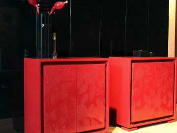 Two red cabinets with decorative pieces on top of them