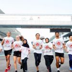 People running on a track wearing a common teshirt with writings on it