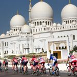 Cyclists riding in colorful jerseys with a white marble mosque in the background