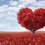 Blue skies with a red heart shaped tree, red hills and red grass