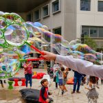 Hand shot of a bubble maker making bubbles with kids looking at the bubbles in the background