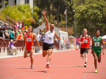 Athletes running on a red track with a winner in white vest rasing his one hand up in motion