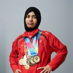 An athelete in red jacket and black head scarf posing with meadls around her neck